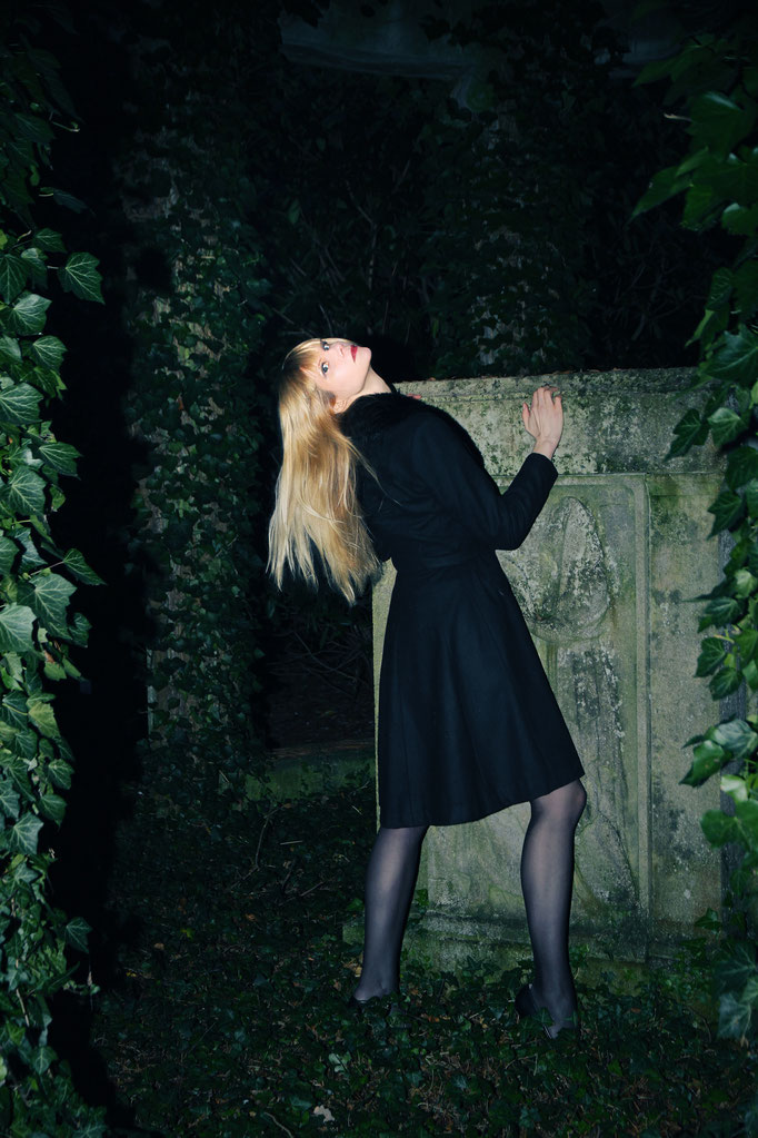 Blond woman at a cemetery, her back is to the watcher-but her had turns toward the photographer. She is wearing a black coat.