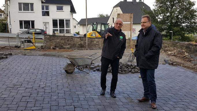 Ortsvorsteher Franz Linneboden zeigt Stefan Redder die Fortschritte auf dem vorderen Teil des Schulhofes