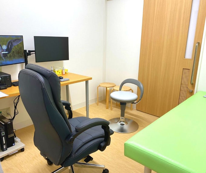 落ち着いた白い壁と木目の床に、鮮やかな黄緑色のベッドがおかれ、とても落ち着いた雰囲気の診察室になっています。