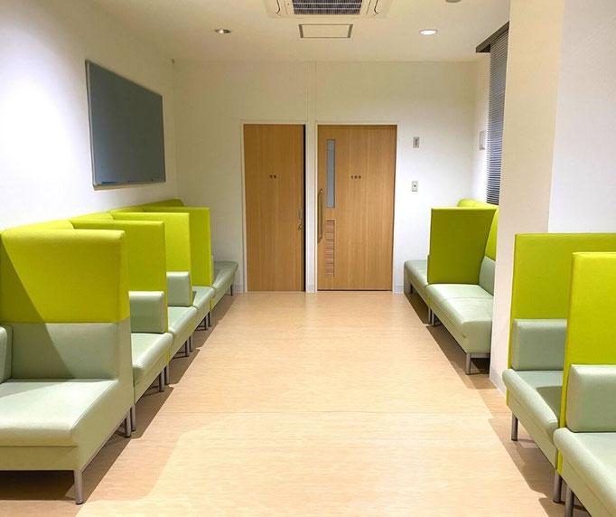 風除室から待合に入ると、パーテーションのある緑色のソファーが並び、木目の床と建具の色合いが合って、とても綺麗です。