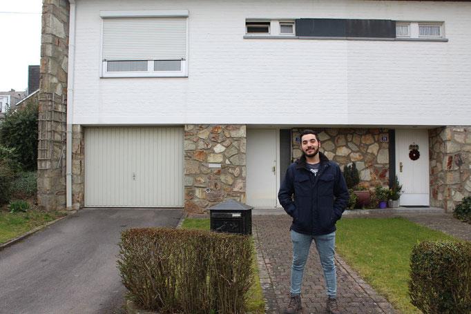 Khalid steht stolz vor seinem Haus in Eupen