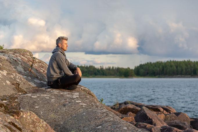 Mann meditiert oder ist achtsam und im einklang mit der Natur um sich zu entspannen und etwas gegen den Stress zu tun.