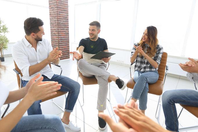 Team Resilienz-Coaching mit Männern und Frauen, die im Stuhlkreis sitzen und einen Lösungsweg für ihr Problem finden.