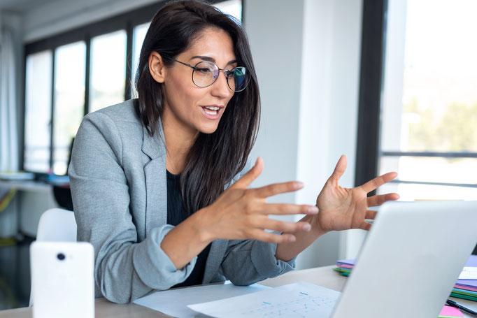 Frau sitzt an ihrem Laptop auf der Arbeit und nimmt an einem Resilienz-Coaching oder Resilienztraining teil, sie gestikuliert und scheint sehr vertieft zu sein.