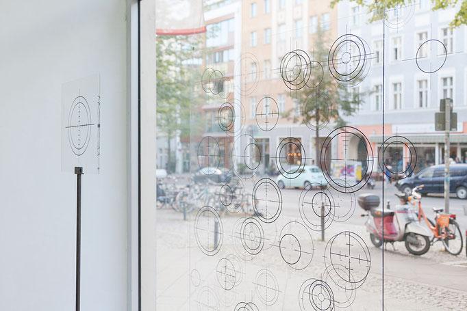 """Francis Zeischegg · """"Focussing Grids"""" 135 x 120 x 8 cm, Acrylglas, beidseitig bedruckt, vor Folienplot auf Fensterscheibe und freistehend Acrylglasobjekt auf Stativ, 30 x 30 x 180 cm, Acrylglas, einseitig bedruckt, Kanten poliert, 2018"""