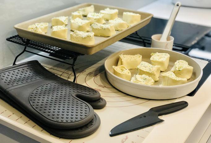 Hier siehst du meine vorbereiteten Käse-Schnecken und alle Produkte die ich hierfür verwendet habe: Teigunterlage, Nylonmesser, Silikonpinsel, Silikonhandschuhe PacksAn, Kuchengitter, großer Ofenzauberer und die runde Stoneware Leila