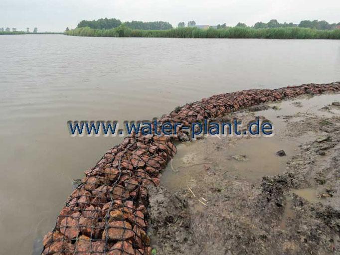 Steinwalzen bilden die neue Uferlinie