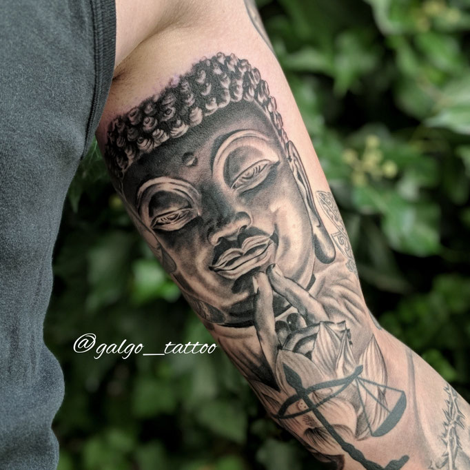 tatu realista de un Buda, hecho en black and grey en el interior del biceps.