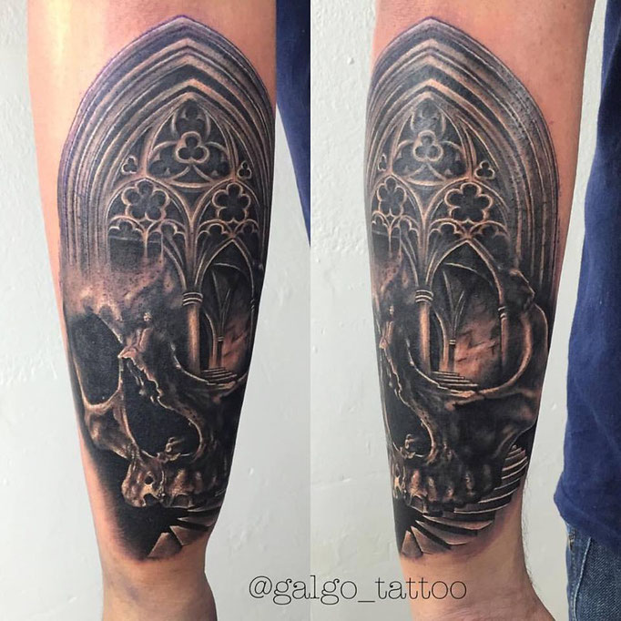 Realistic tattoo of a skull with a gothic arch.