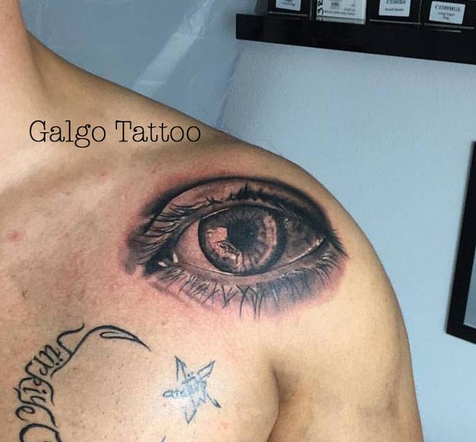 Un buen tatu de un ojo realista en blanco y negro, sobre el hombro.