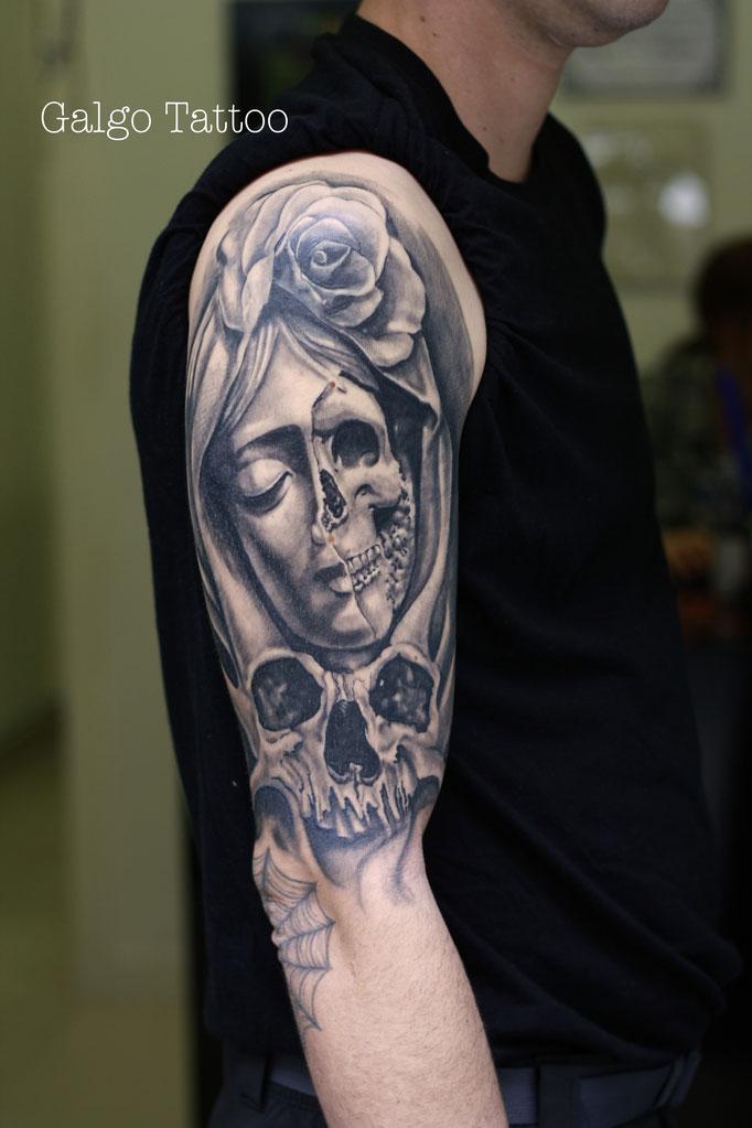 tatuaje de estilo realismo, de una virgen con una calavera y una rosa en el brazo, realizado en Santander, España.