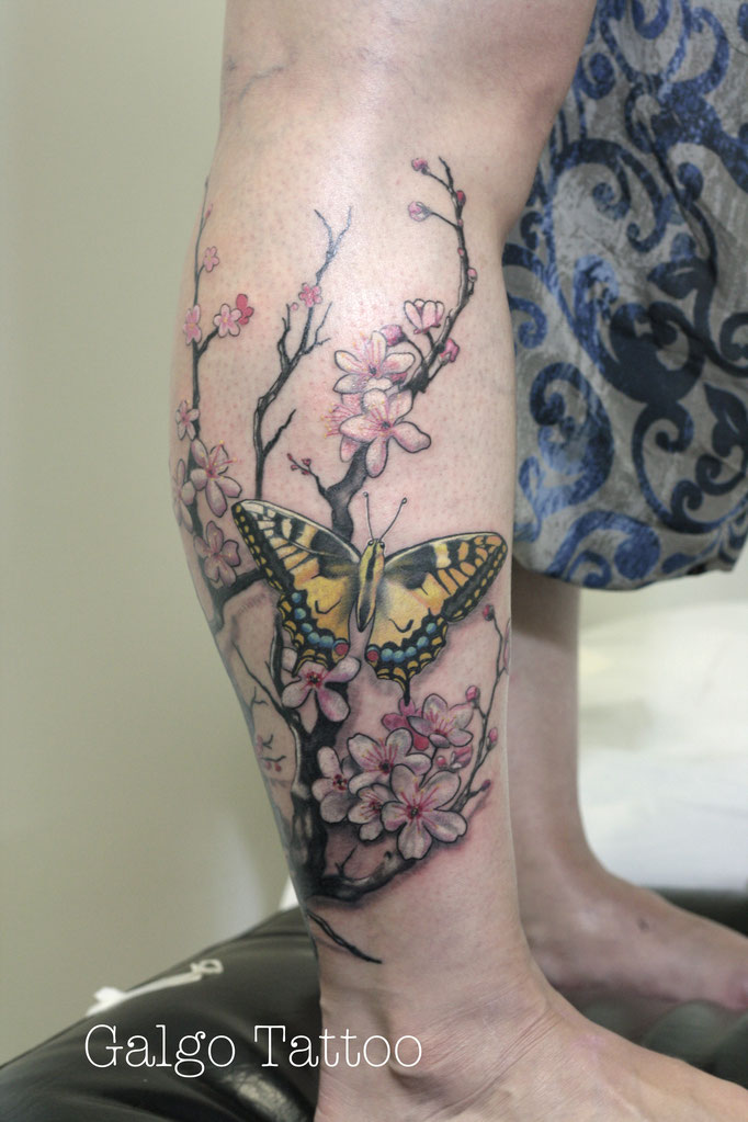 tatuaje realista de una mariposa en color amarillo, posada sobre una rama de cerezo. Realistic tattoo with a yellow butterfly on a sakura tree