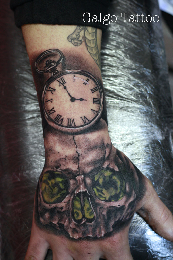 Skull and clock tattoo on the hand.
