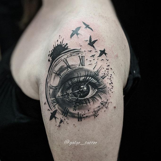 Tatuaje femenino realista con un ojo dentro de un reloj.