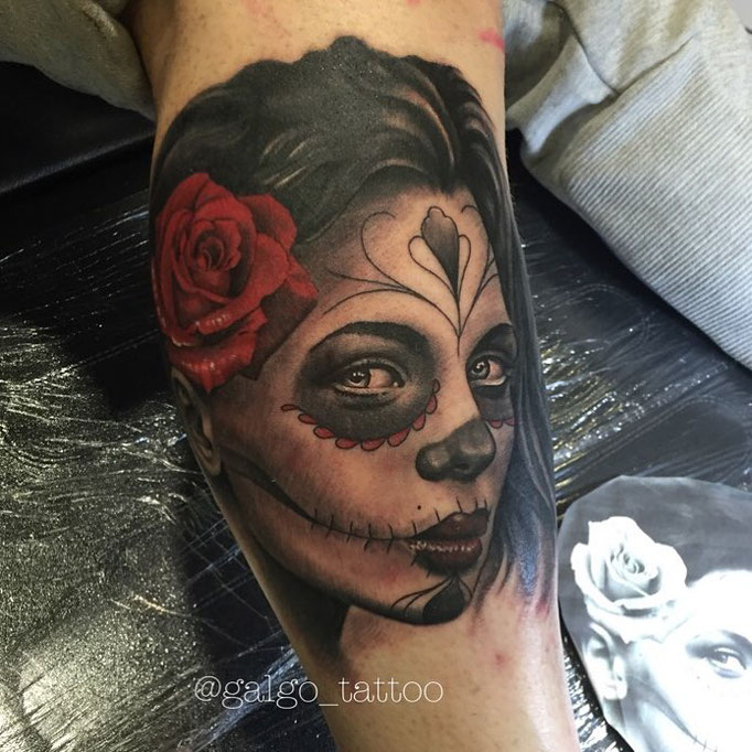3/4 view portrait tattoo of a Catrina. Black and grey work with a red rose.