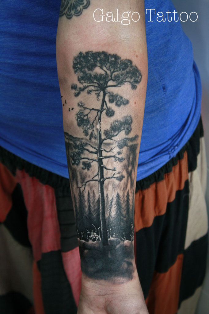 Tree realistic tattoo on the arm with a forest on the background.