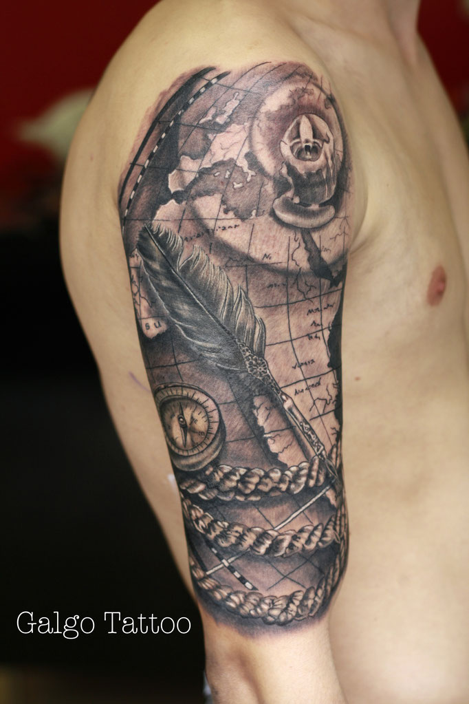 Black and grey relistic tattoo of a map, a compass and a feather.