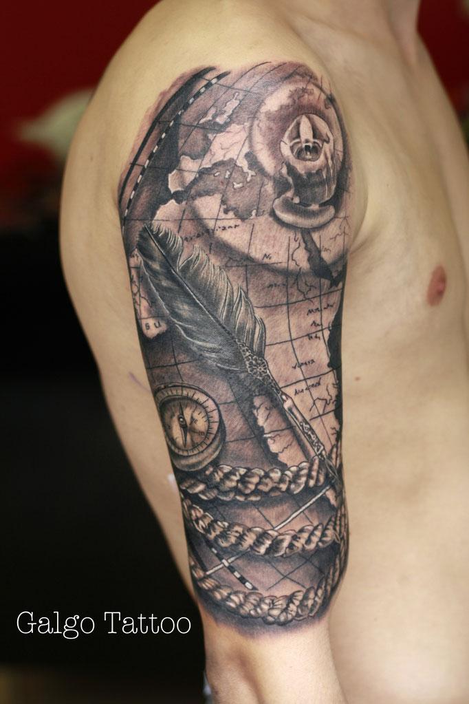 tatuaje de mapa con una brujula y una pluma. Realismo en black and grey.