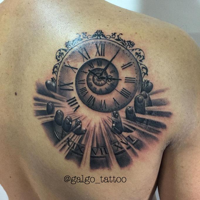Tatuaje de un reloj con la hora de nacimiento, con unas manos que simbolizan la acogida en este mundo.