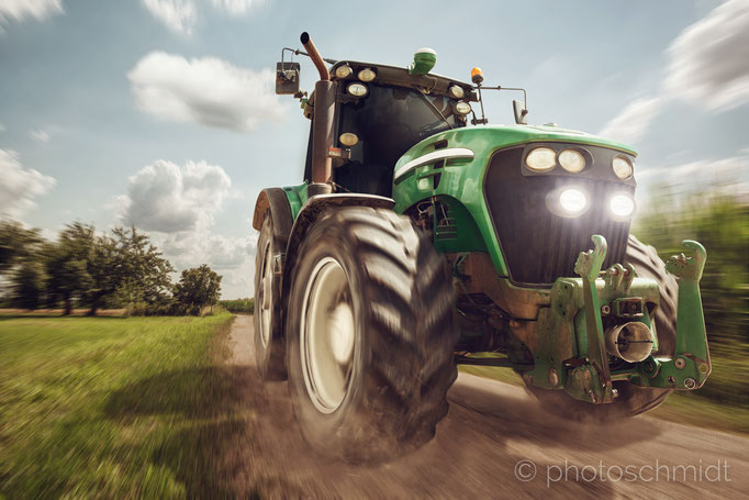 Traktor fährt auf einem Feldweg