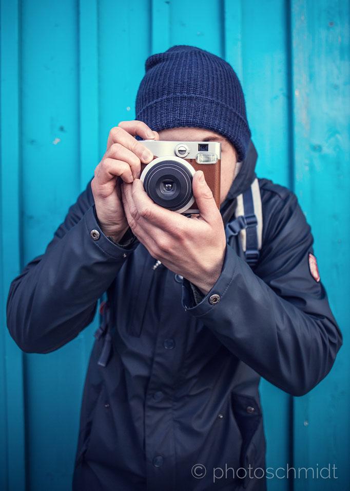 Hipster fotografiert vor blauem Holz-Hintergrund