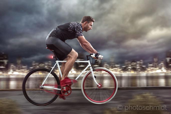 Man mit modernem Fahrrad vor nächtlicher Skyline