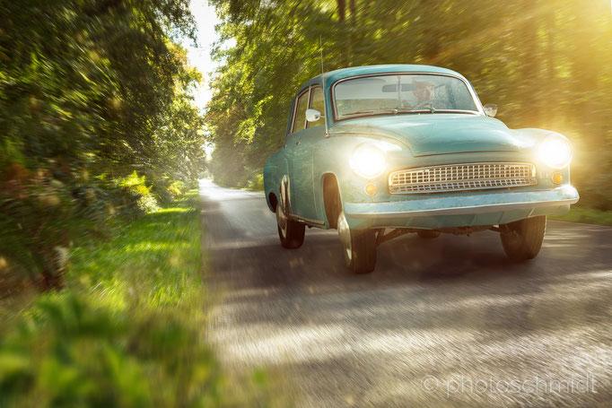 Oldtimer fährt auf einer Straße im Wald