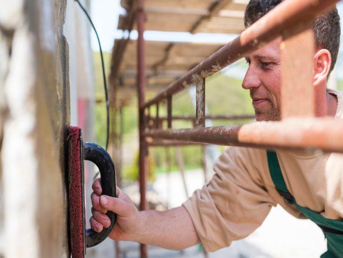 Ein Mitarbeiter der 3B Denkmalpflege & Bausanierung GmbH beim verputzen einer Fassade.