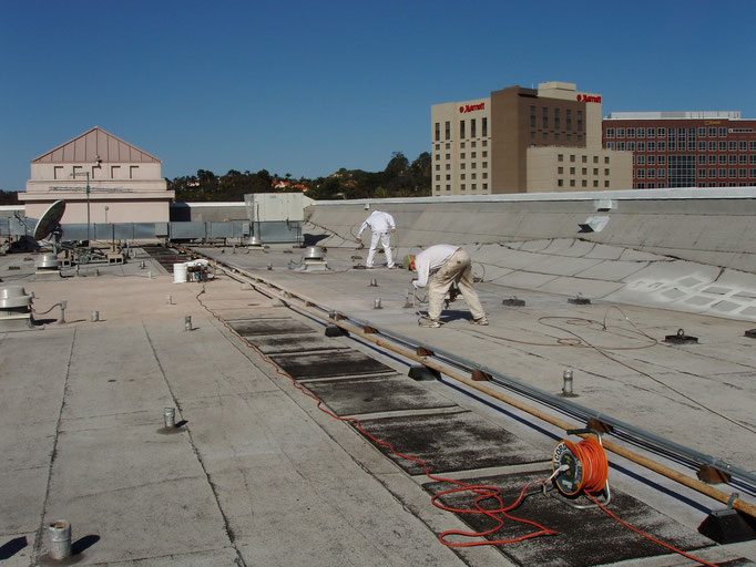 Crew spraying Ceramic InsulSeal on a commercial Built-Up-Roof (BUR) project