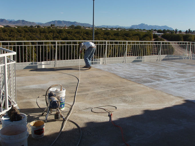 Spraying Ceramic InsulSeal on an asphalt surface