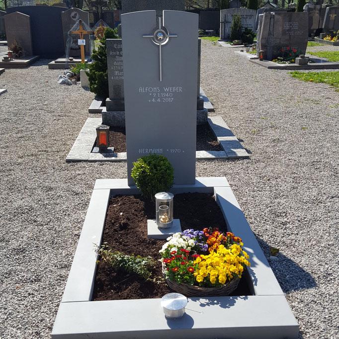 Grabdenkmal in Tobler Sandstein mit einem Durchbruch, damit das strahlende Kreuz aus Edelstahl zur Geltung kommt