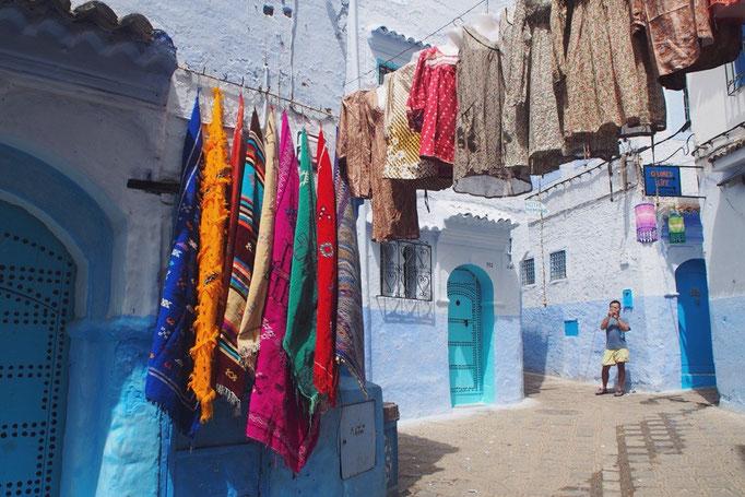 この日は少しお天気が良くなって嬉しい日 お土産屋さんのカラフルな服や布が青い町並みによくお似合い