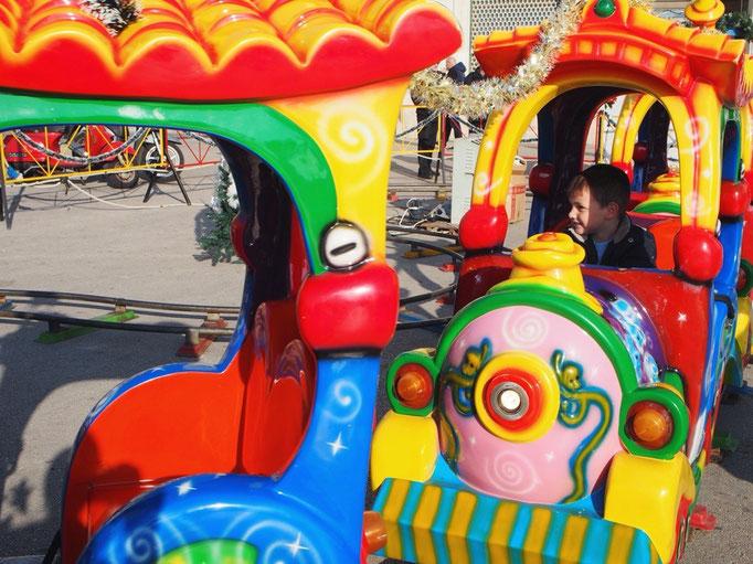 小さな子ども用の列車に乗っている子どもはすごく楽しそうな笑顔♡