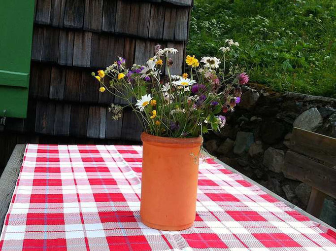 wilde Bergblumensträuße überall auf den Tischen der Trauneralm, die 1890 gebaut wurde.