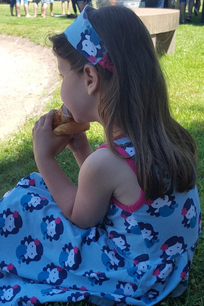 Unsere Kleine stärkt sich auf dem Flohmarkt mit einer Bratwurst
