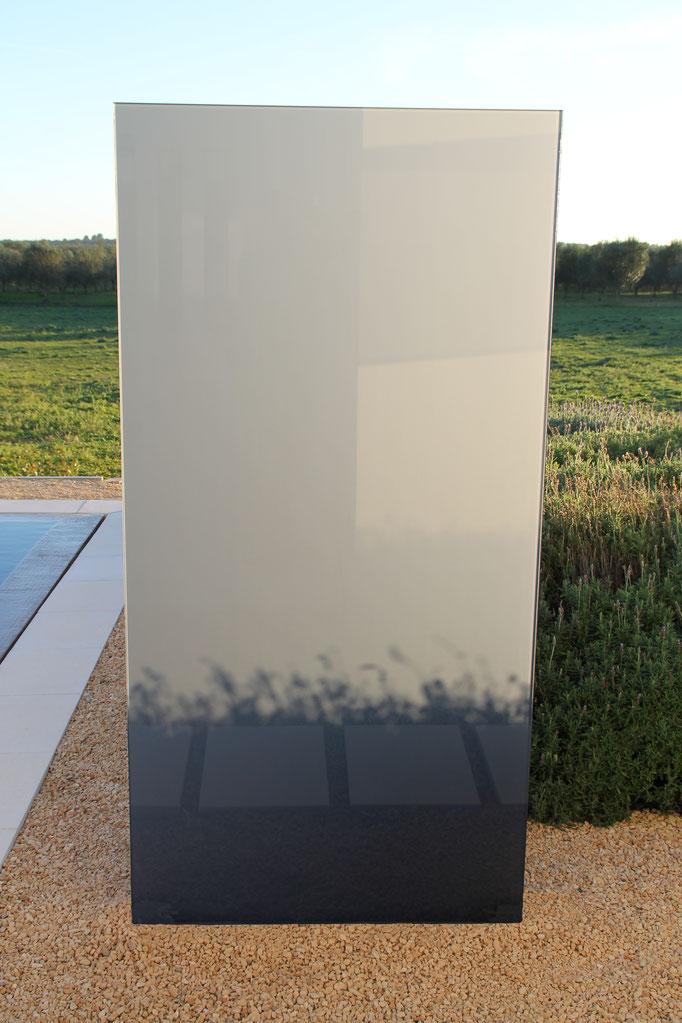 Glasstele im Garten spiegelt sich