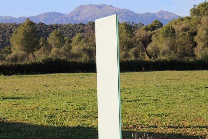 Glasstele mit Bergen im Hintergrund