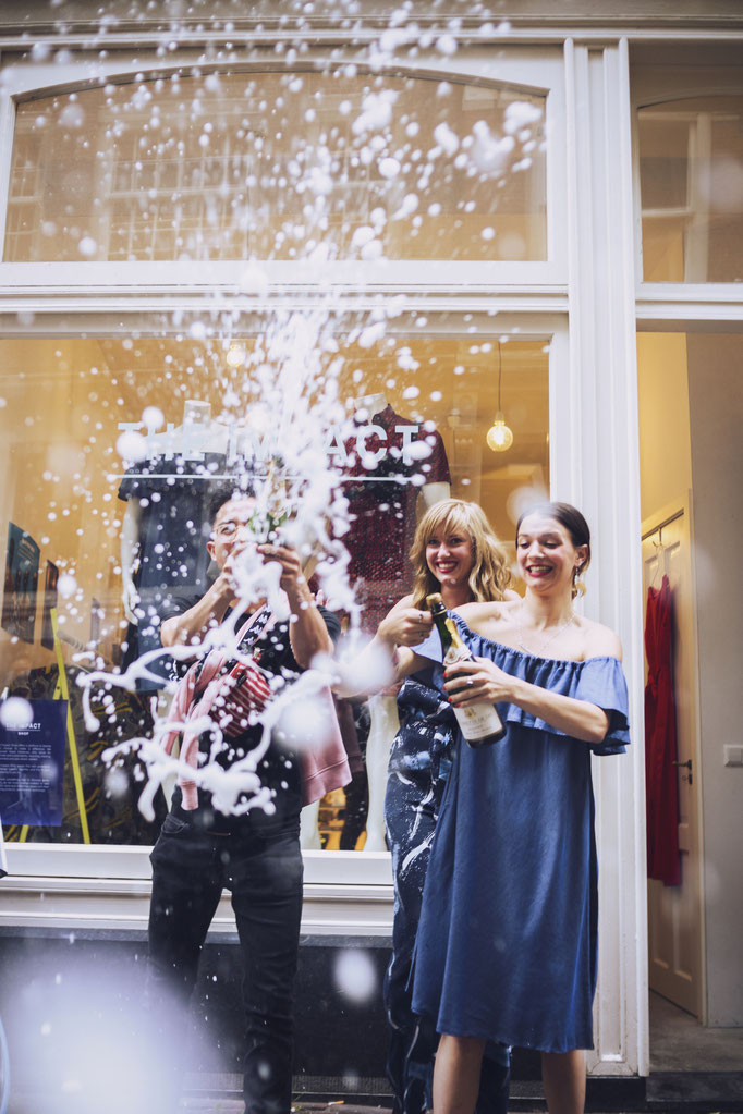 Chanel Trapman and Lisa Elsenburg popping champaign at the opening of The Impact Shop by photographer Landa Penders in Amsterdam