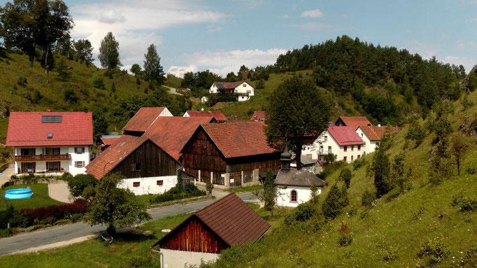 Links Ferienwohnungen und rechts die Dorfkapelle