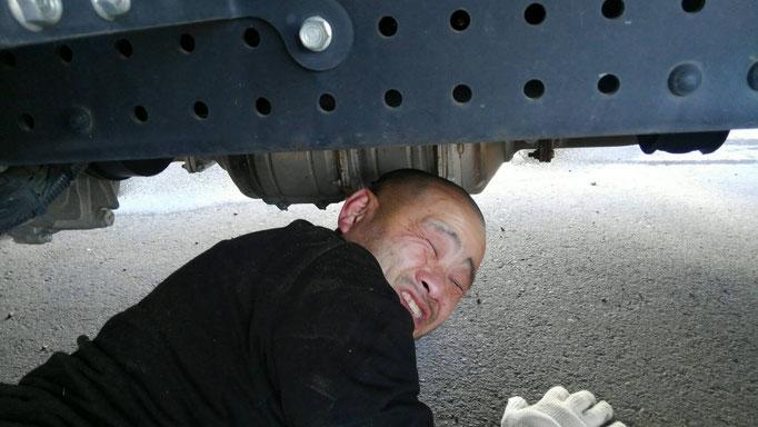 トラックの下に潜る男性