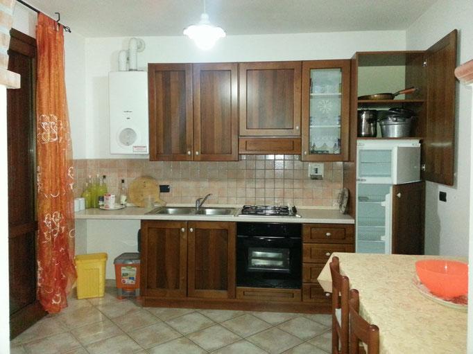 cucina a gas, forno elettrico, frigo, freezer, lavello, microonde, stoviglie
