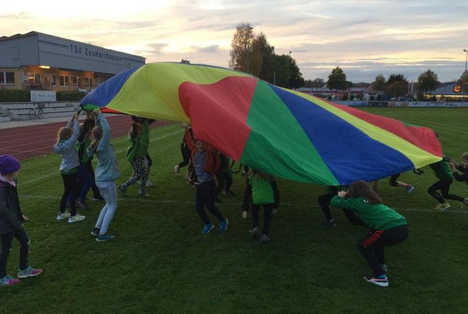 Die jungen Leichtathleten freuen sich über ihr neues Schwungtuch.
