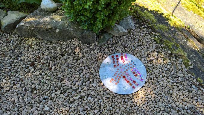 Kinder machen schöne Mosaikteller für den Garten