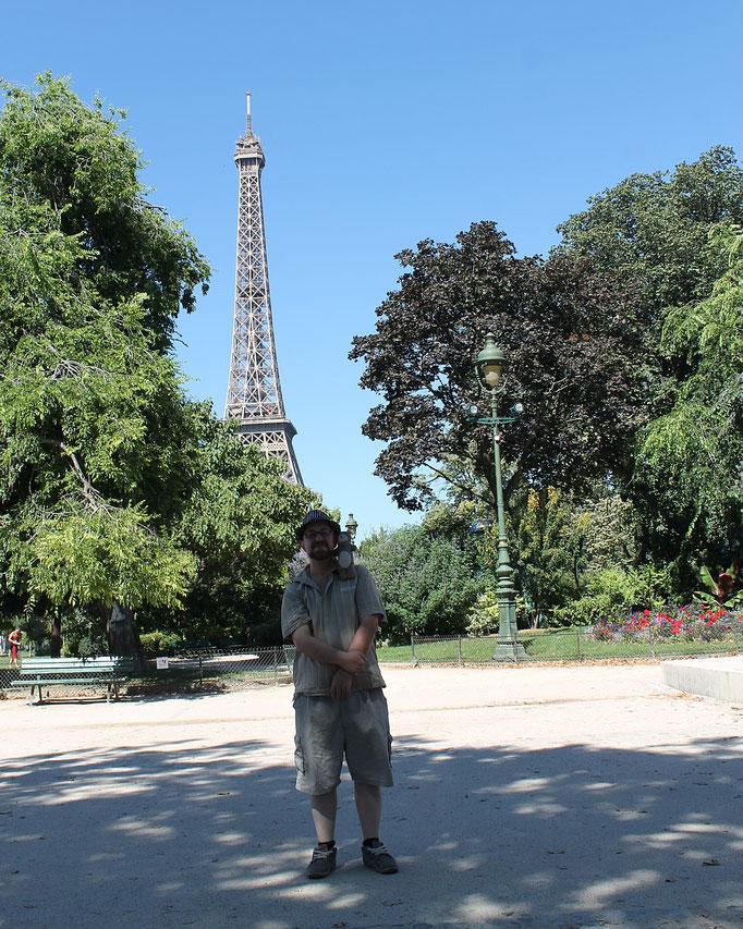 Un jeune homme à Paris au pied de la Tour Eiffel avec Moka la loutre version peluche pour le collectif d'artistes et créateurs