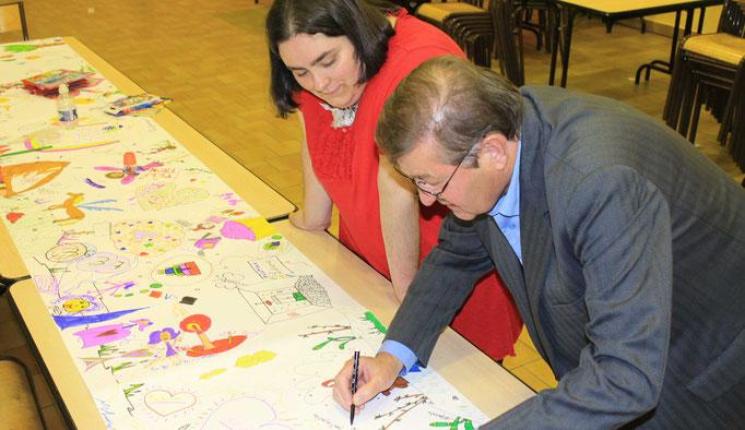 Mr le Maire de St Père dans la Nièvre écrit les remerciements avec l'illustratrice Cloé Perrotin sur la fresque du téléthon 2016