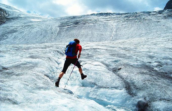 Sprung über einen Eisbach vor der Kulisse des unteren, inzwischen abgeschmolzenen Eisfalls