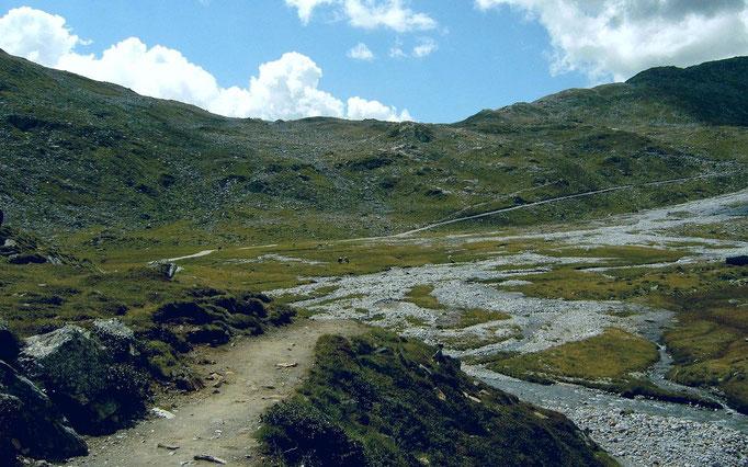 Weiter hinten führt der Weg durch ein flaches Hochtal mit mäanderndem Bachlauf
