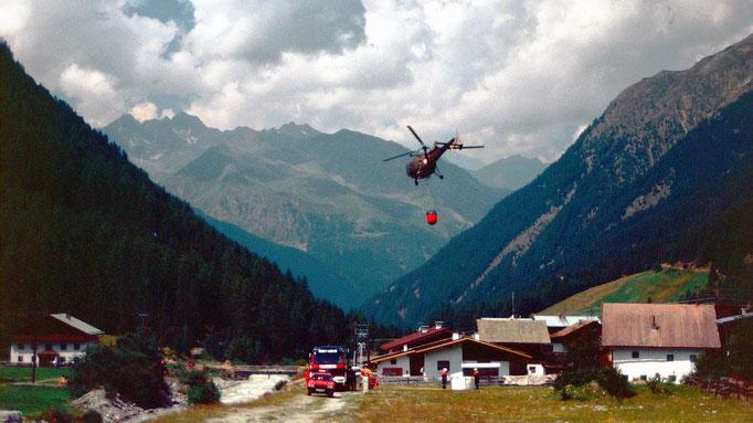 Hubschrauber im Sulztal im Löscheinsatz wegen eines kleinen Waldbrands in einer steilen Bergflanke