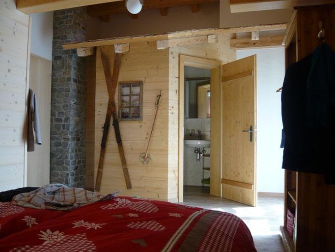 """Schlafzimmer """"Alpenstübli"""" mit eingebuatem Swiss Chalet und Badezimmer"""