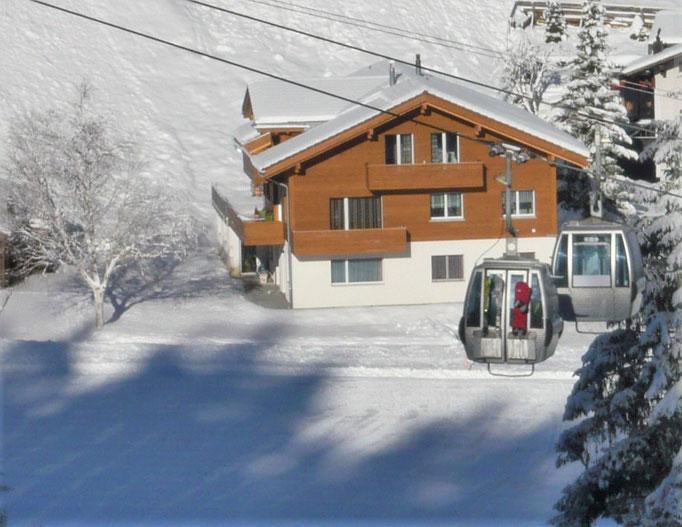 Ansicht Winter: 300 m bis zur Talstation Bergbahnen Adelboden und Skipiste bis vors Haus.